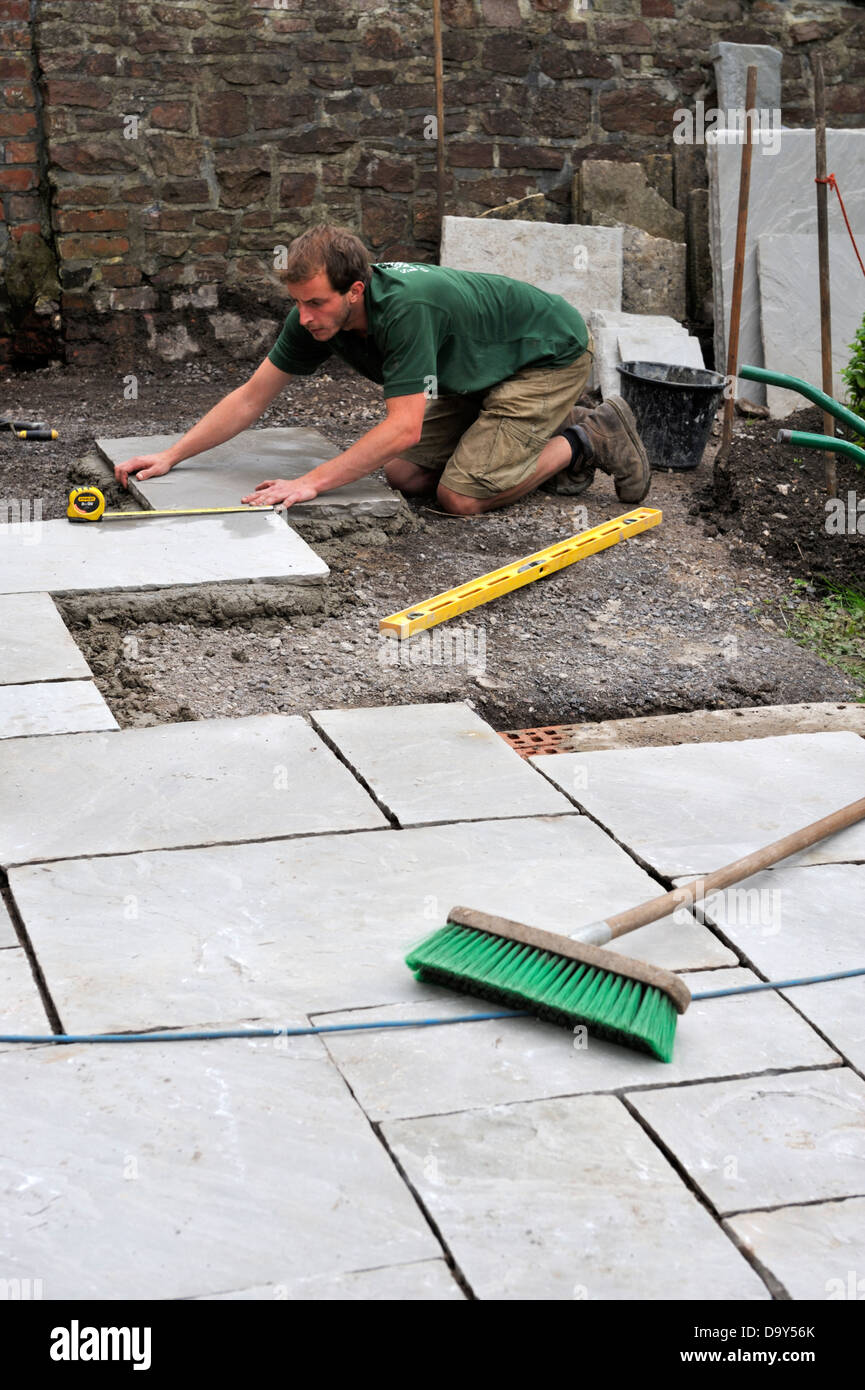 Laying Natural Stone : Construction of a patio laying natural stone paving man