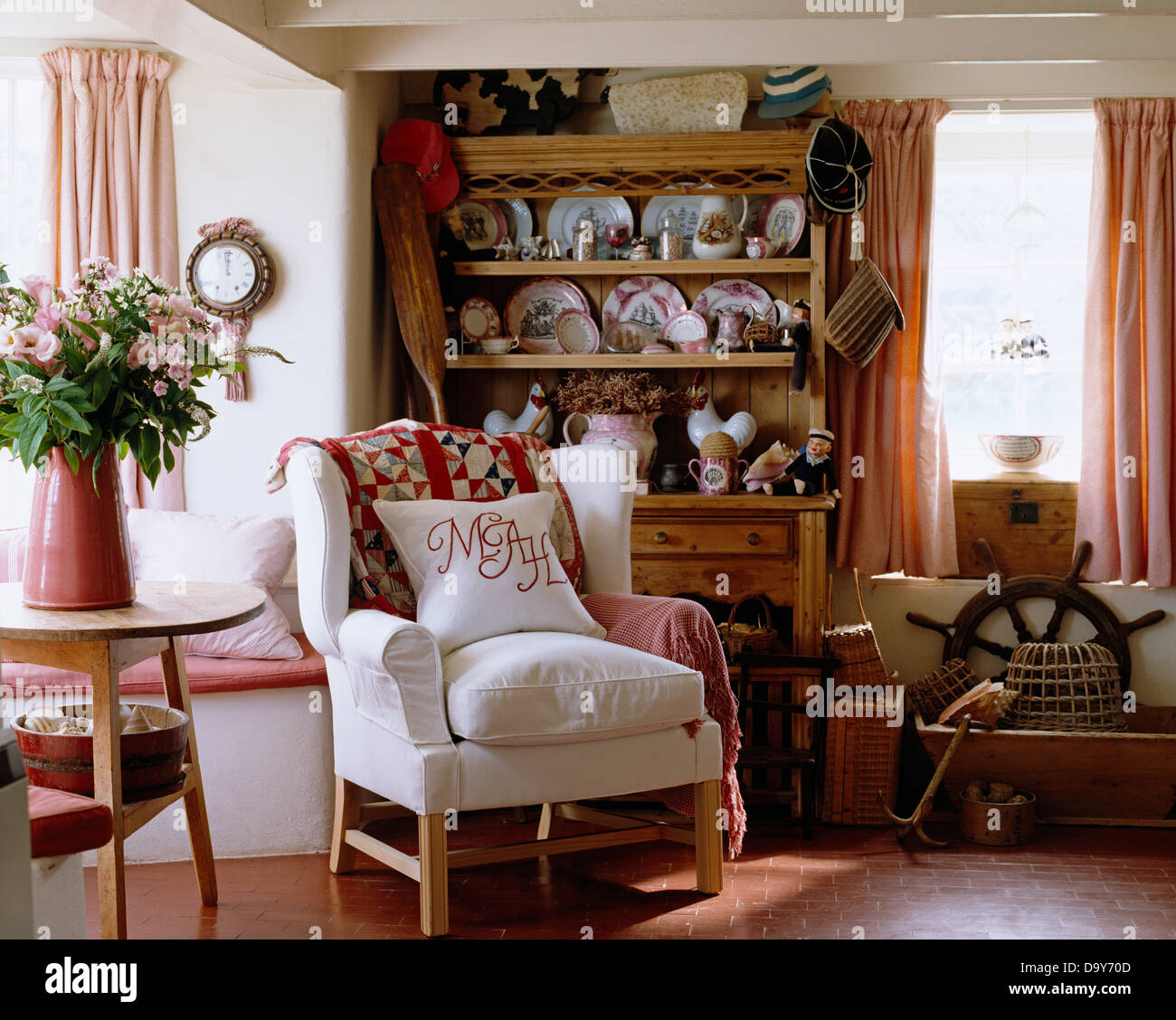 Monogrammed White Linen Cushion On Upholstered Armchair In Cottage Living Room With Display Of Pottery Pine Dresser