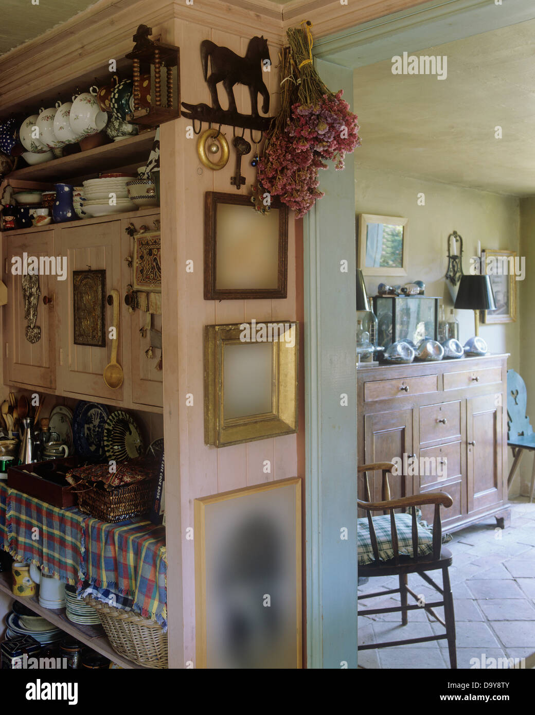 Pink Cabinet In Country Kitchen With Dried Flowers And Picture Frames On Wall Beside Doorway To Dining Room Sideboard