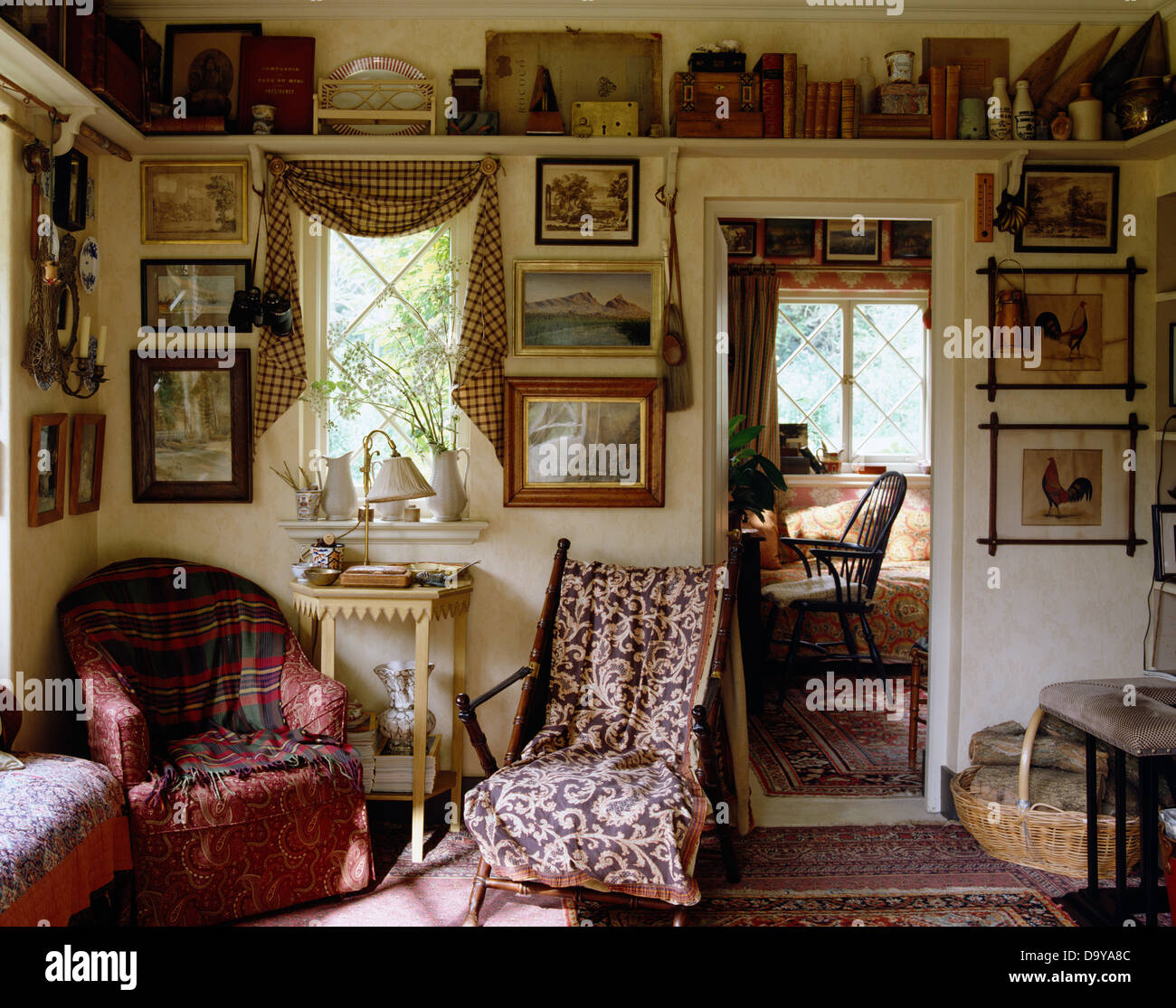 Tartan Throw On Red Armchair In Cluttered Living Room With Antique