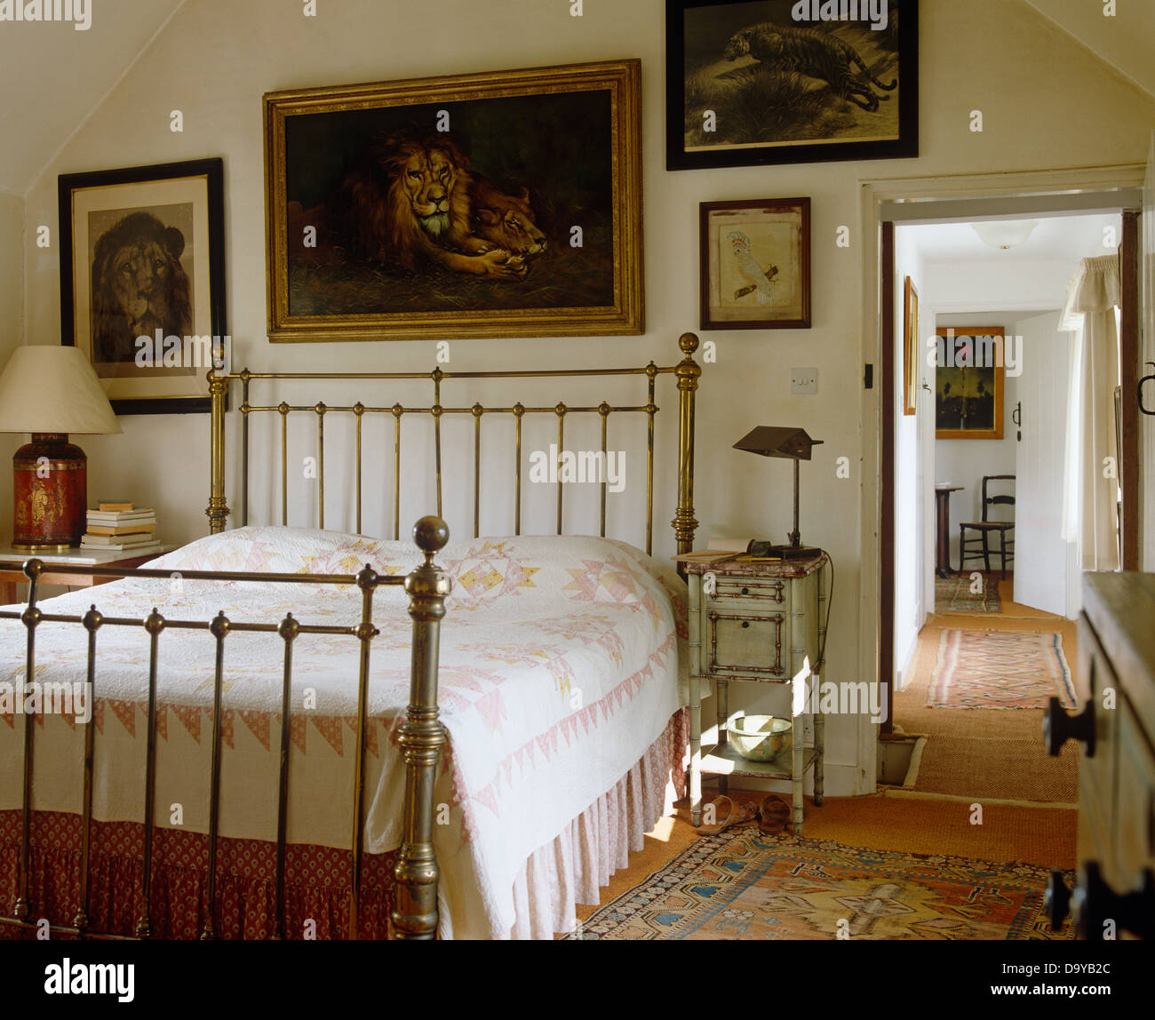 paintings of lions on wall above brass bed with white and pink quilt in country bedroom