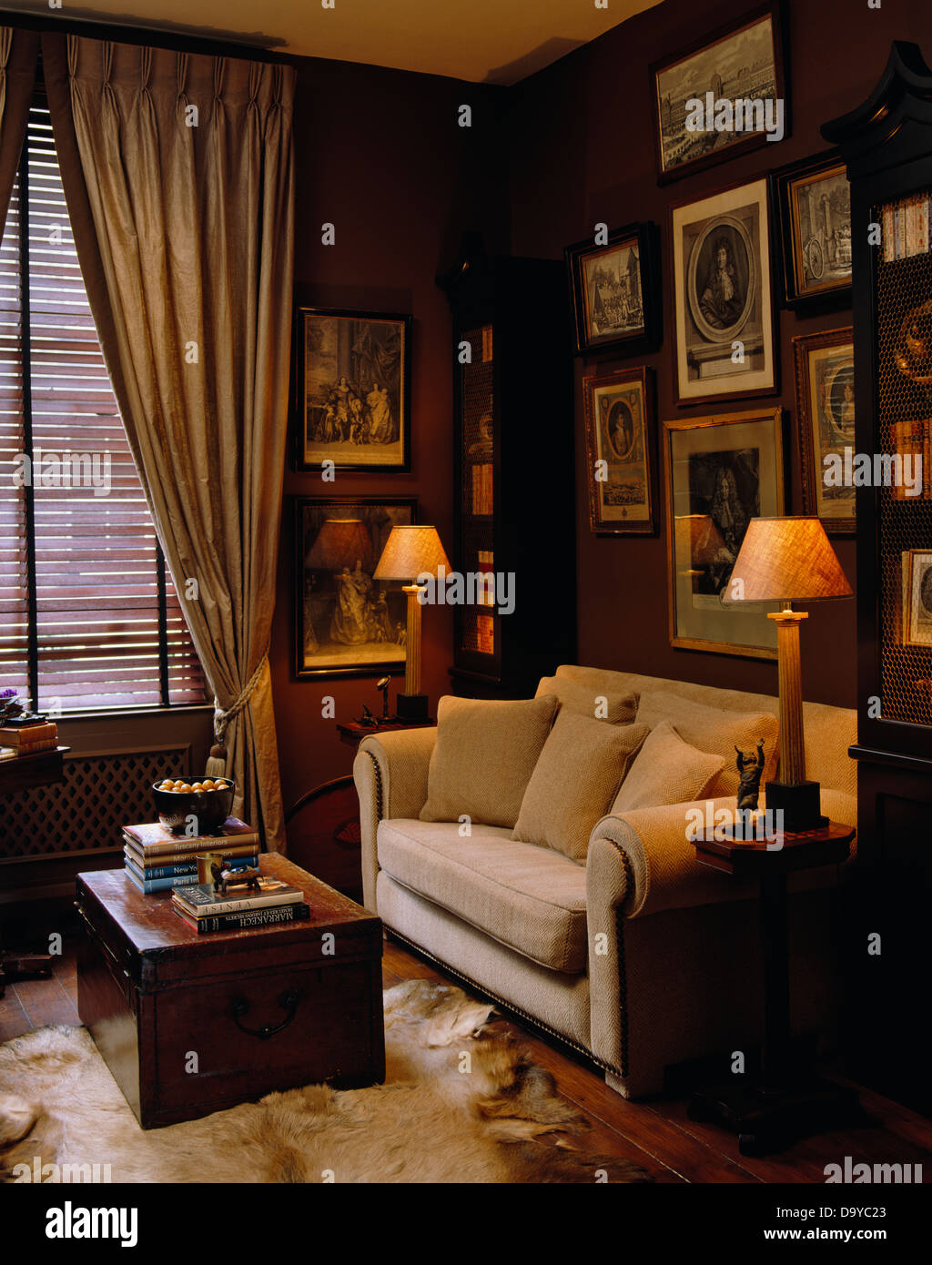 Lighted Lamps On Either Side Of Sofa Facing Wooden Chest Used As Coffee Table In Living Room With Beige Silk Drapes Window