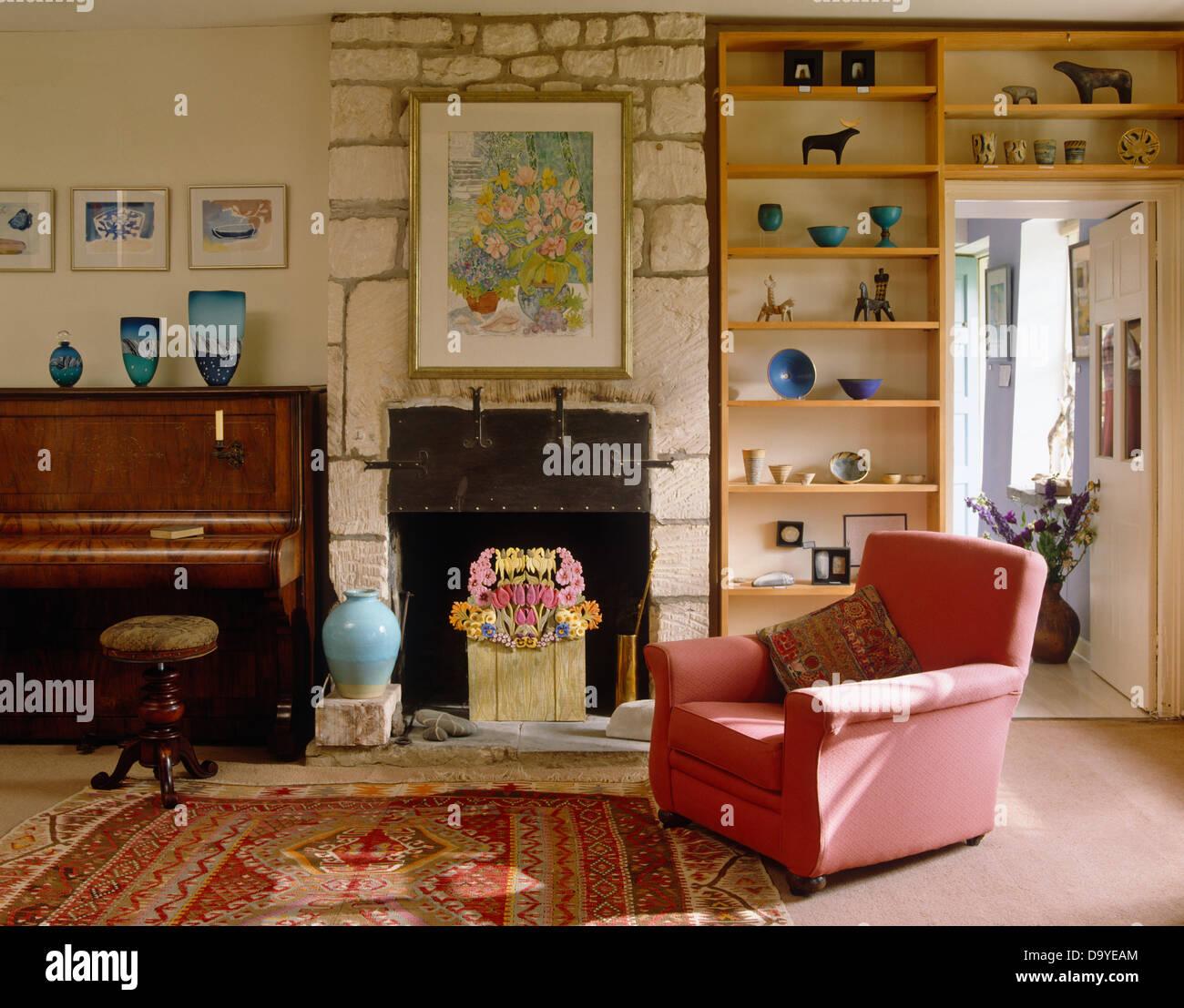 Pink Armchair And Open Wall Shelves In Country Living Room With Piano Beside Fireplace Exposed Stone