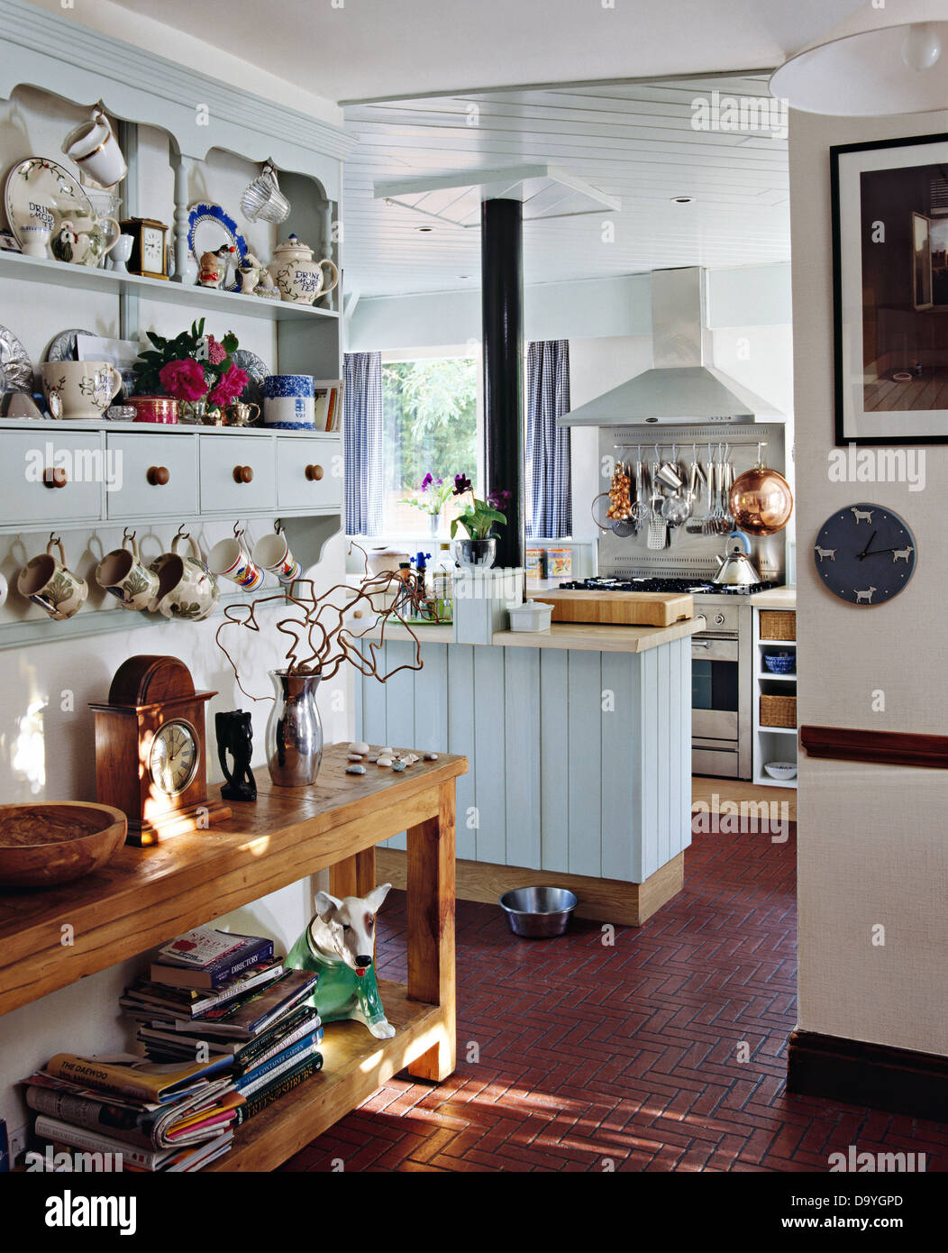 crockery on shelves of painted wall cupboard above simple wood console D9YGPD