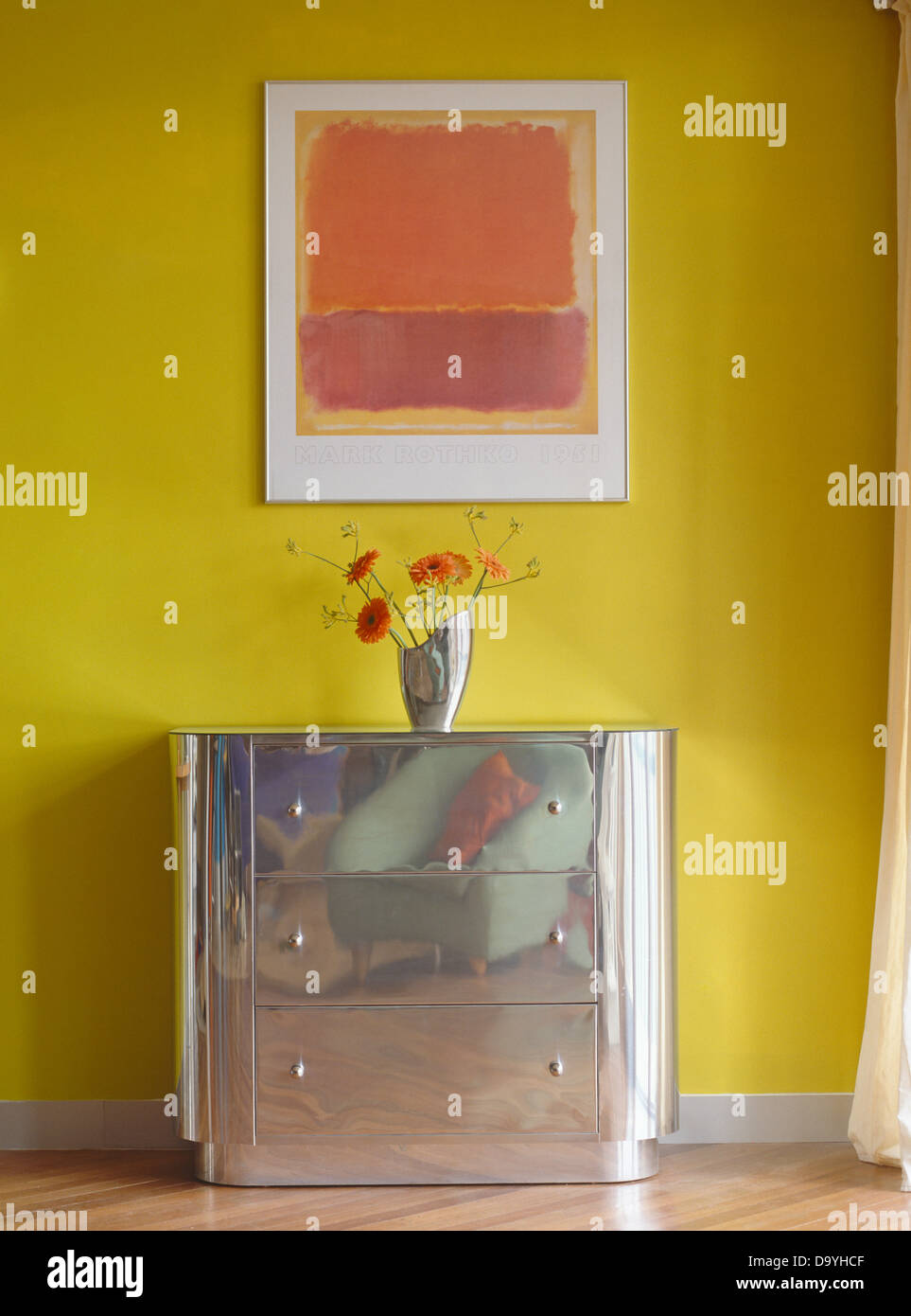 framed rothko print on wall above chest of drawers with vase of flowers against vibrant yellow wall