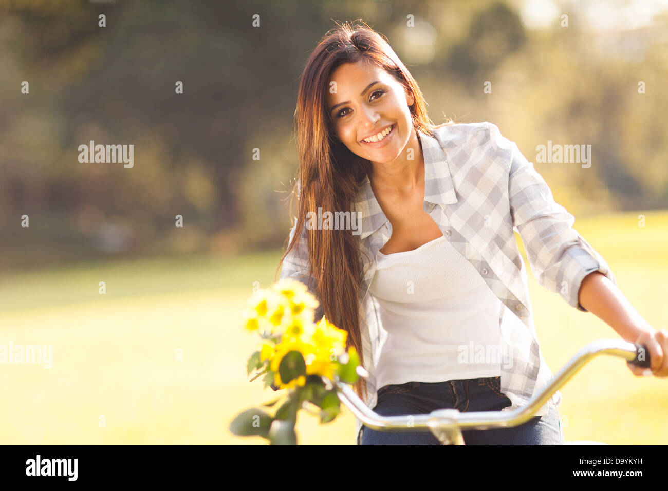 Beautiful woman with flowers riding a bicycle in a park stock stock photo beautiful woman with flowers riding a bicycle in a park dhlflorist Gallery