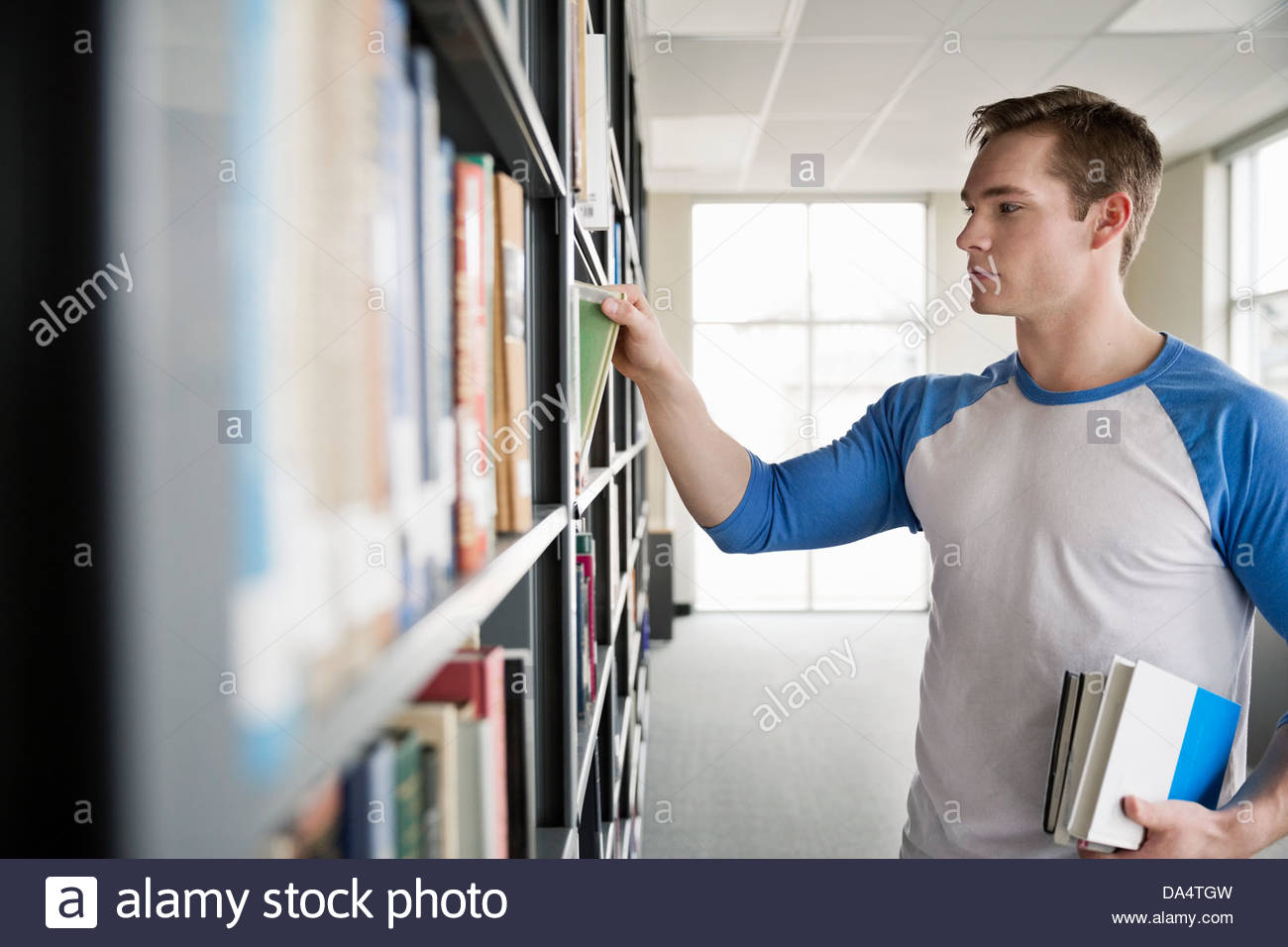 male student choosing books in college library stock photo male student choosing books in college library