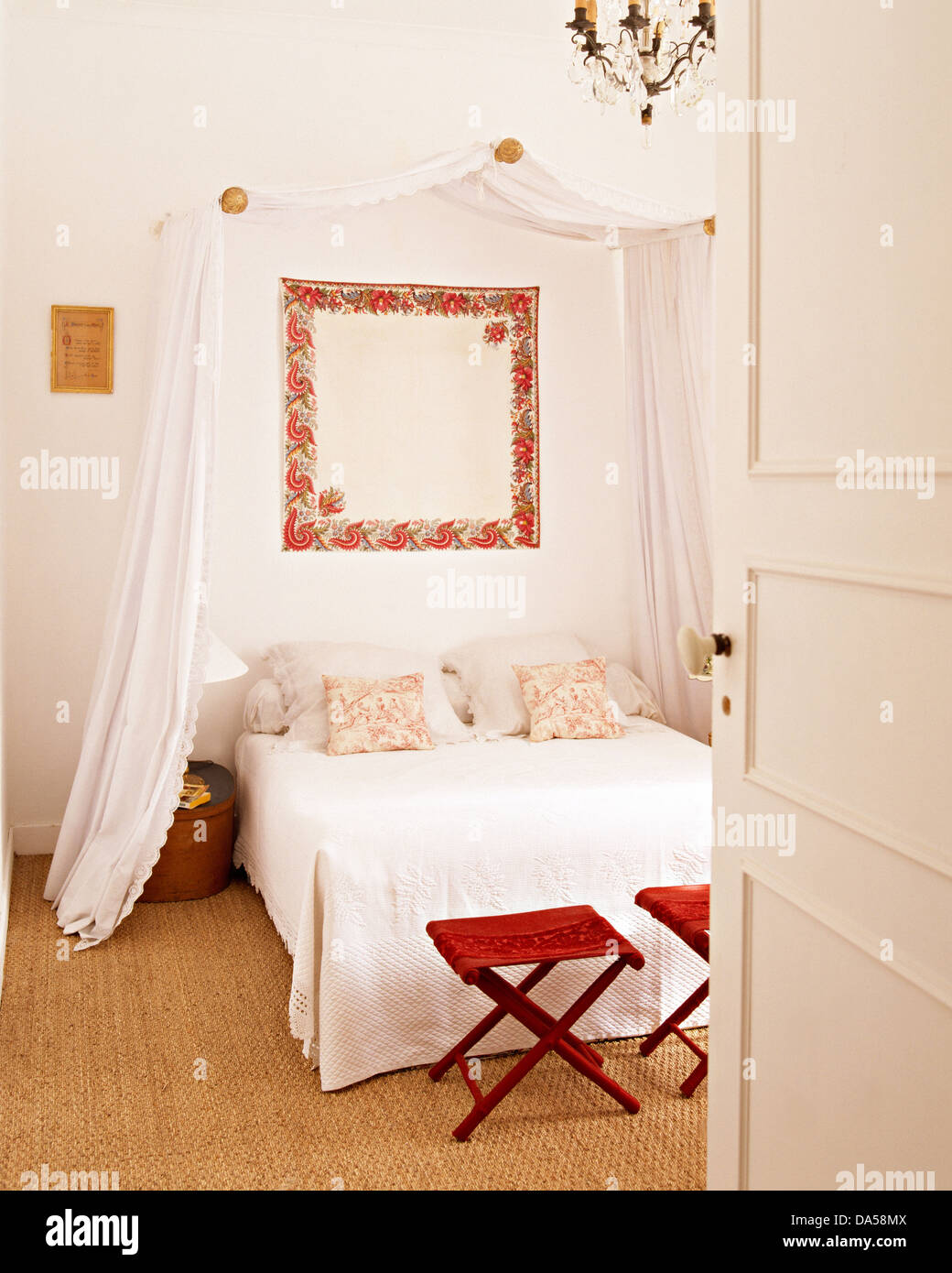 door open to bedroom with white drapes on canopy above bed with