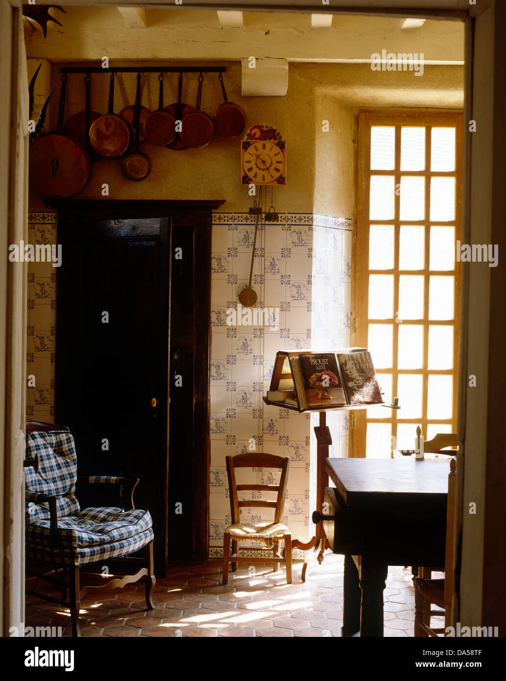 View Through Open Doorway To English Country Dining Room With Blue+white  Tiled Wall And Chair With Blue Checked Cushions