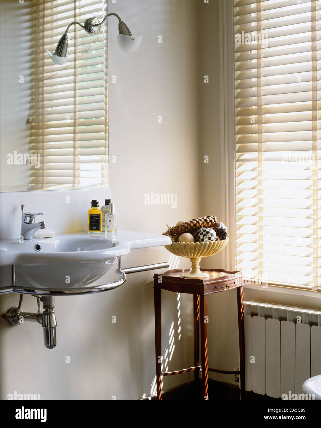 Stainless steel ornaments - Mirror Above Small Washbasin On Stainless Steel Shelf In Modern Bathroom With Vase Of Ornaments On Wooden Side Table
