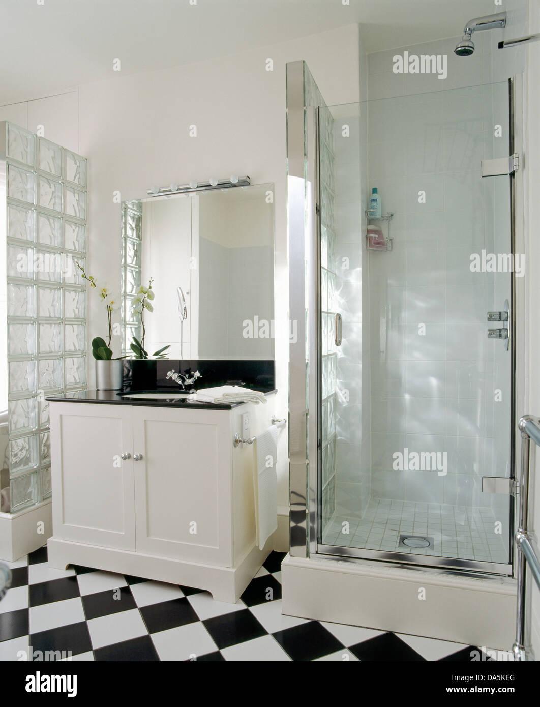 Mirror above wash basin in white vanity unit beside glass shower cabinet in  modern bathroom with black white checkerboard floor. Mirror above wash basin in white vanity unit beside glass shower