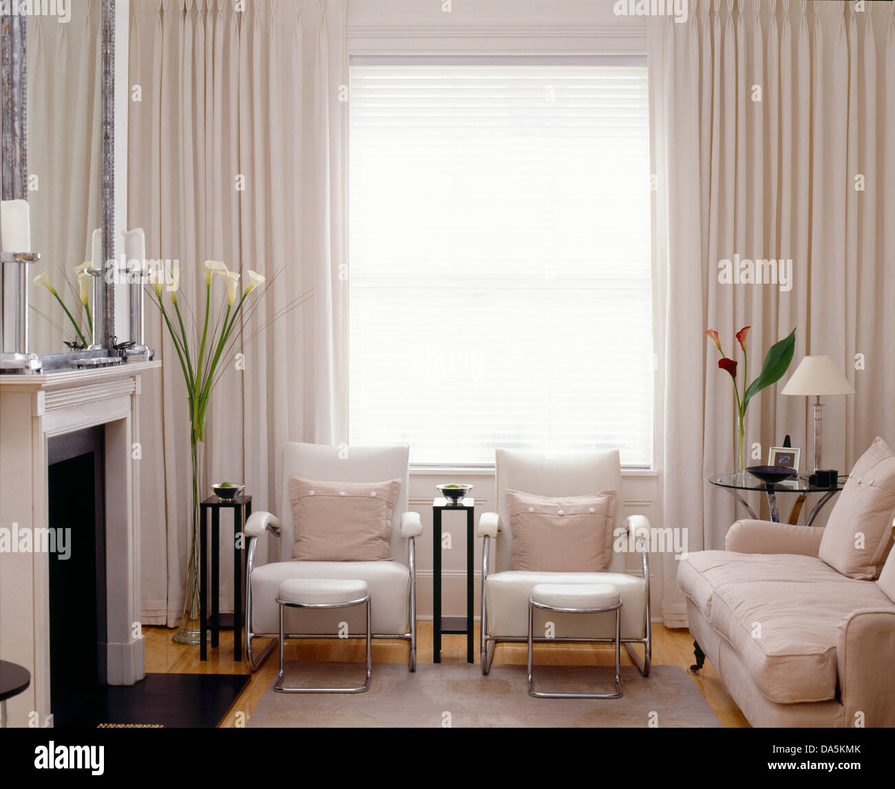 white chrome armchairs and white sofa facing fireplace in modern