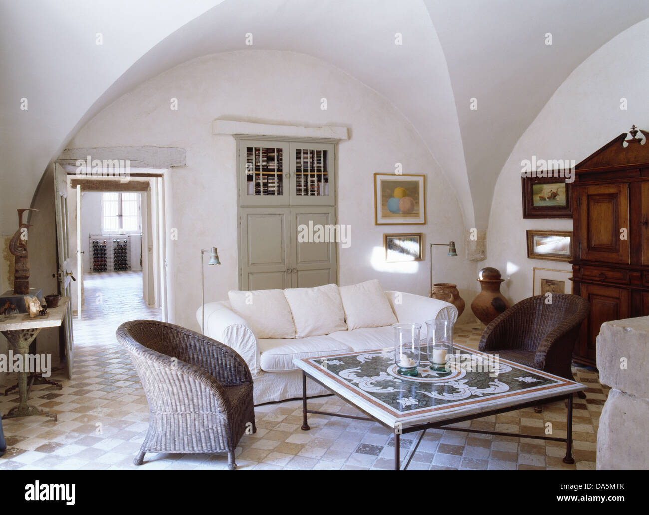 Grey wicker armchairs and white sofa around tiled coffee table in grey wicker armchairs and white sofa around tiled coffee table in white french living room with tiled floor and vaulted ceiling dailygadgetfo Image collections