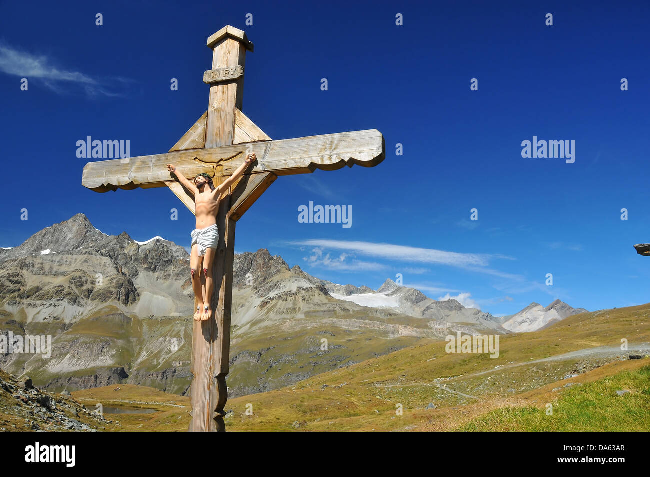 cross with jesus christ crucified in the mountains above a lake