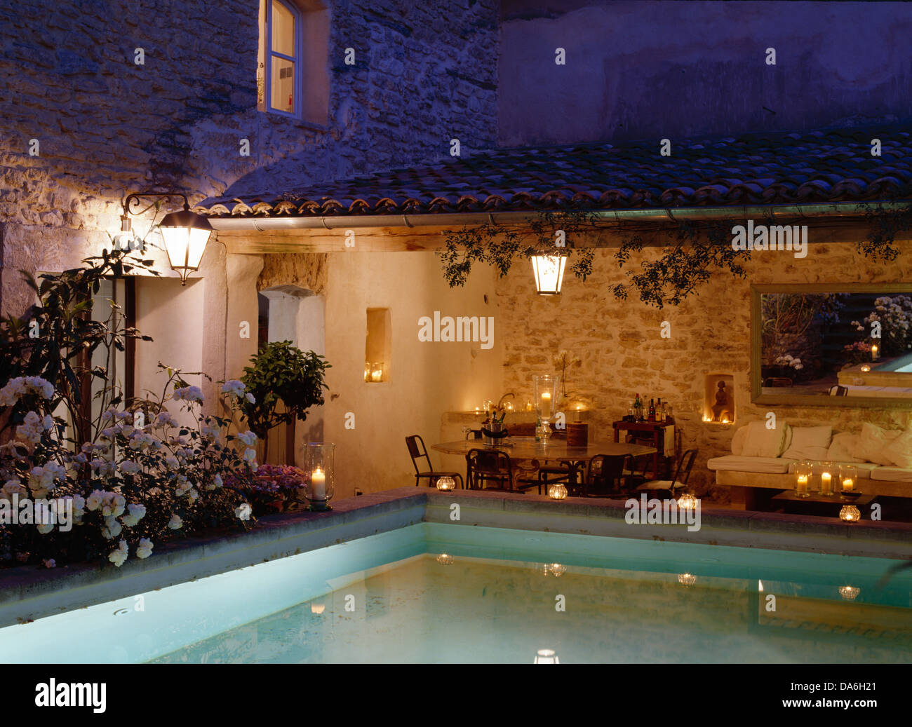 Lights Around Swimming Pool Of French Country House With Table Set For  Candlelit Dinner On Veranda