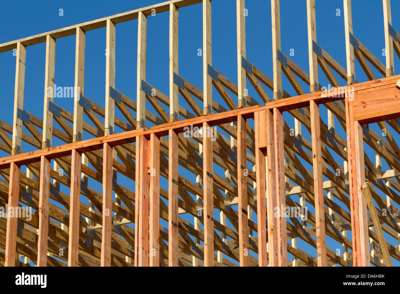 a wood frame building under construction against clear blue sky - Wood Frame Building