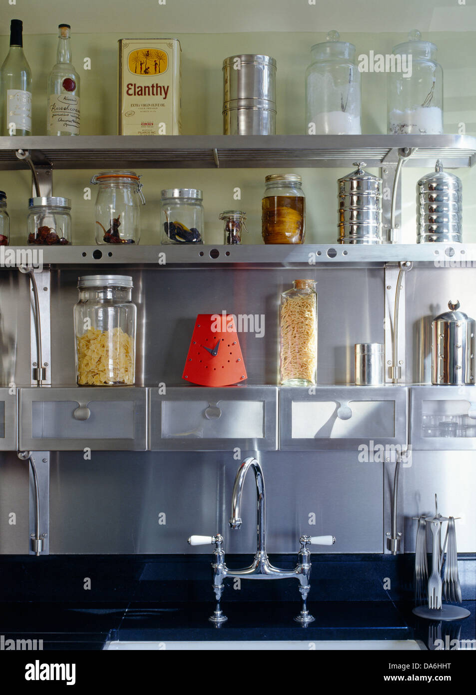 glass storage jars and tins displayed on steel shelving above kitchen sink with chrome taps