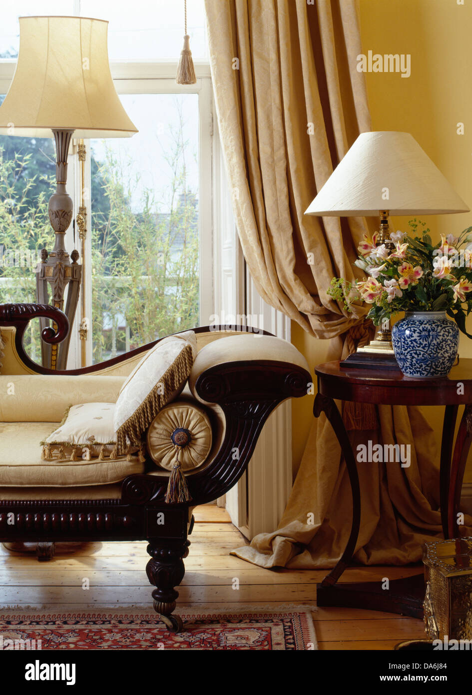 Vintage Chaise Longue And Antique Side Table In Front Of Window With Cream  Curtains In Traditional Living Room