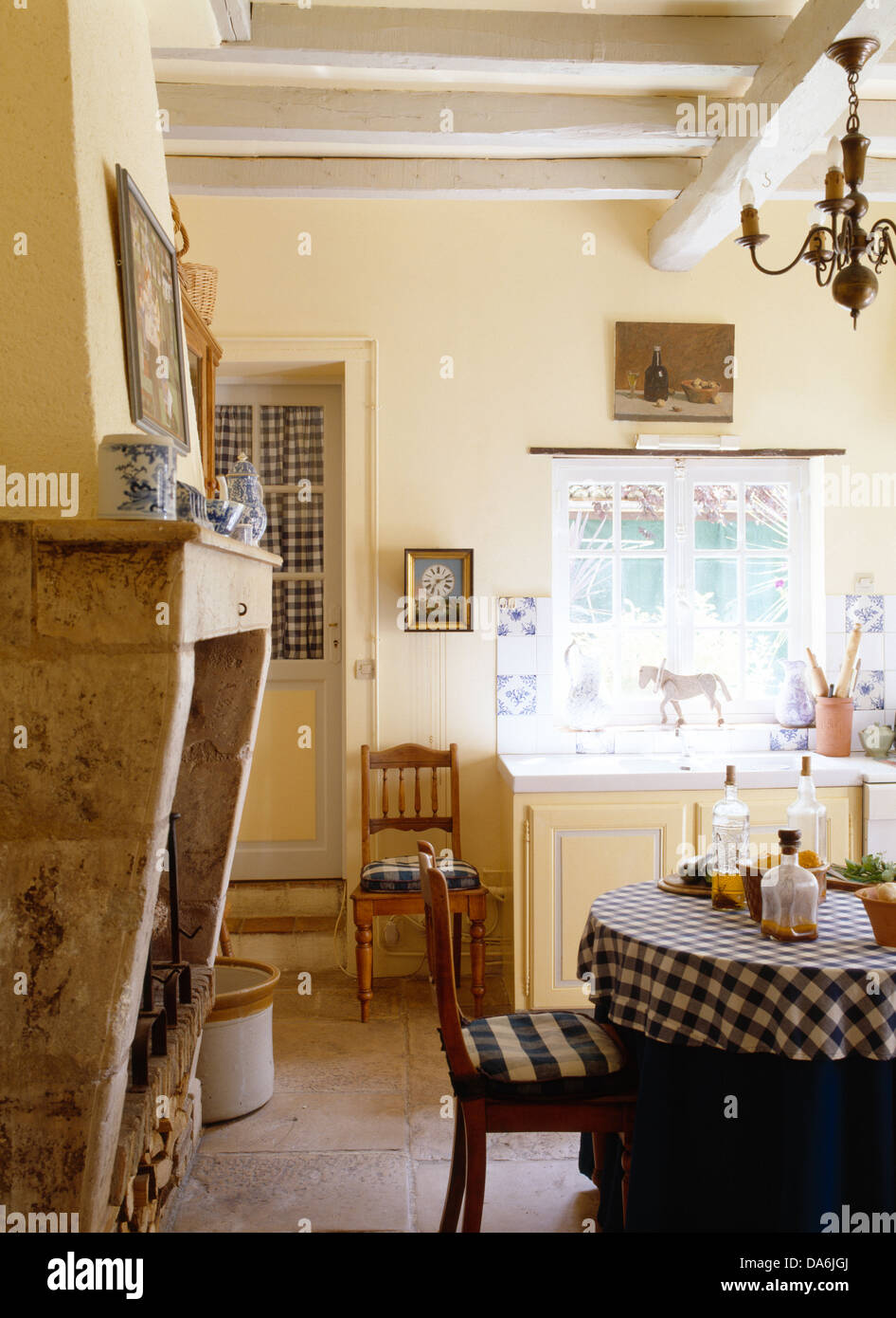 stone fireplace and white painted beams in country kitchen with