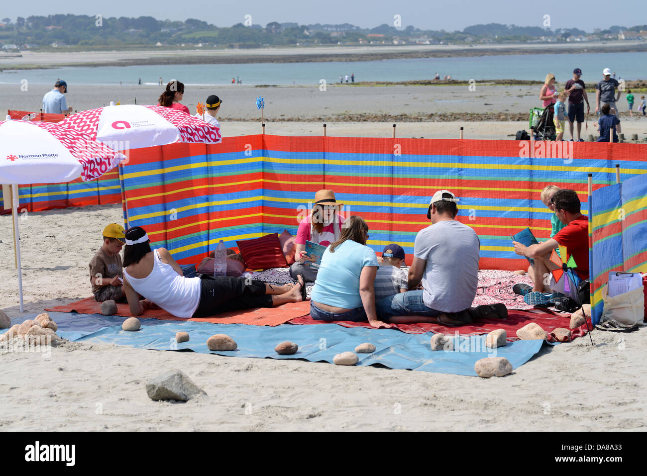 Holidaymakers On The Beach With A Windbreaker On A Sunny Day Stock Image