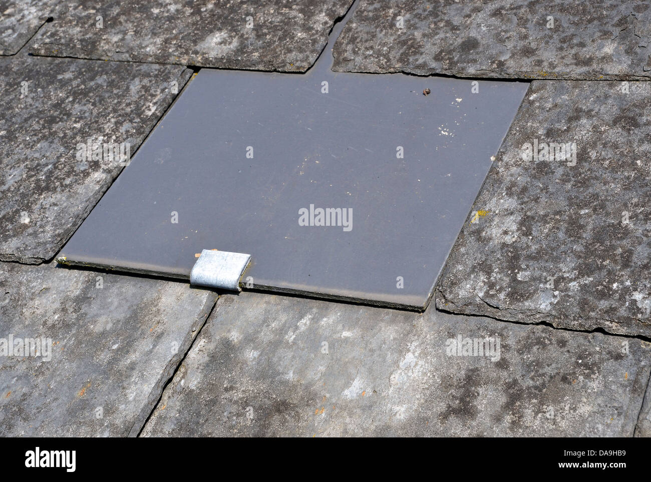 Old Slate Roof Repaired Using A Modern Synthetic Slate And A Lead Strap,
