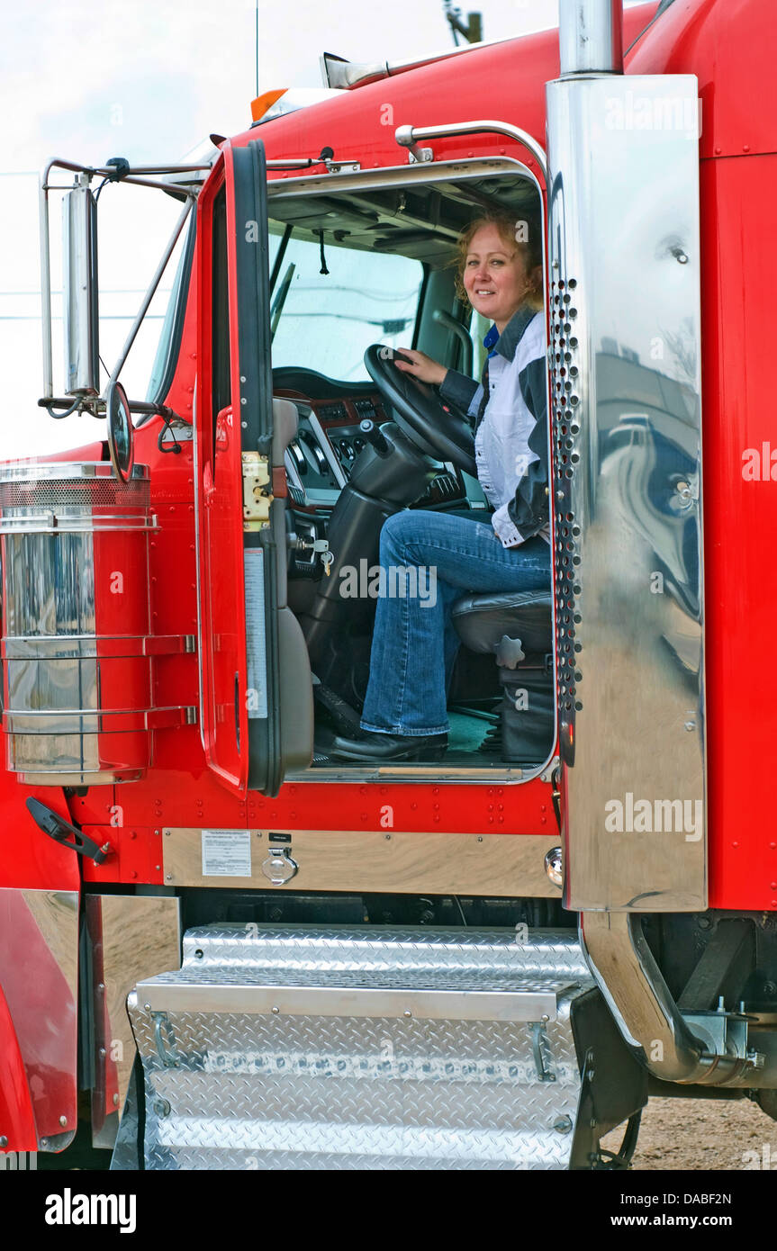 Stock photo woman truck driver looking out the door of a big rig from the driver s seat
