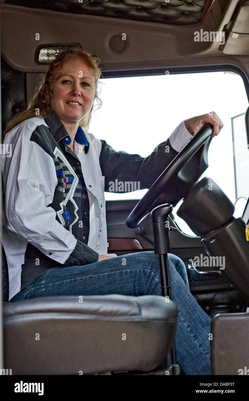 woman truck driver sitting in the drivers seat of a semi truck stock