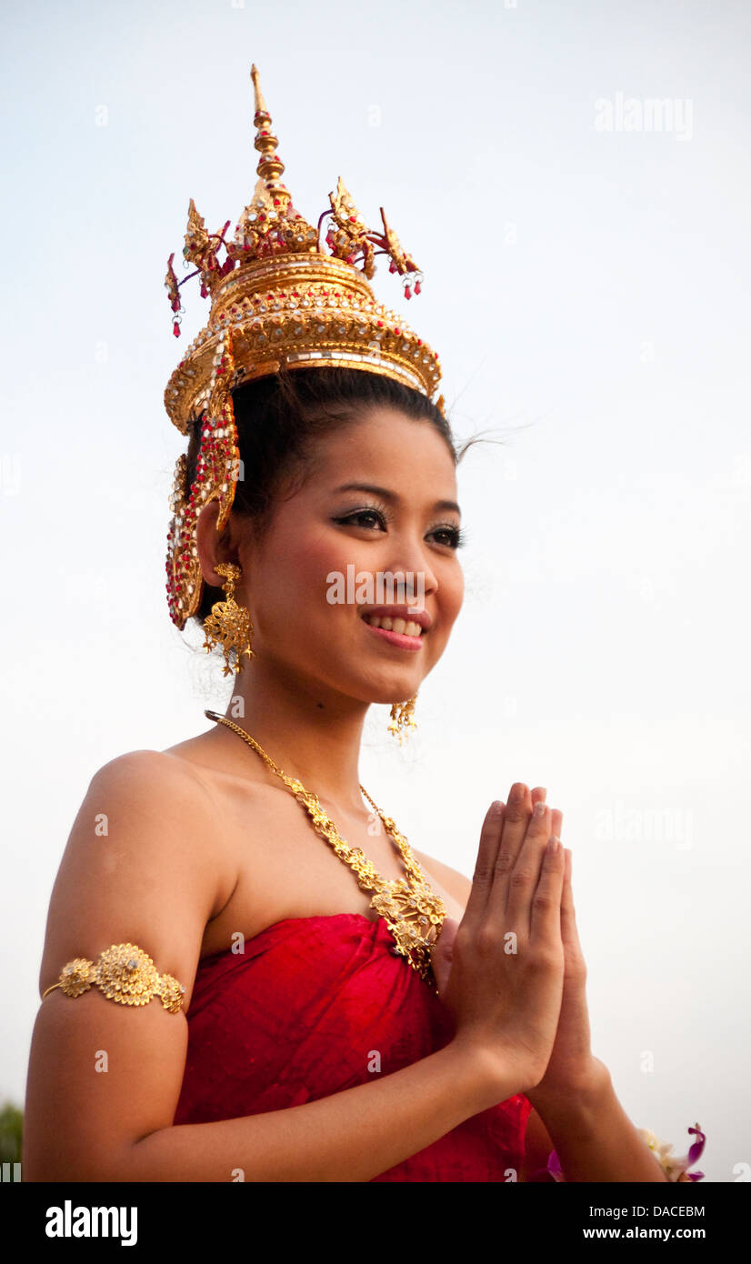 Young thai woman in traditional costume and hands together in wai young thai woman in traditional costume and hands together in wai greeting pose at siam niramit bangkok thailand kristyandbryce Images