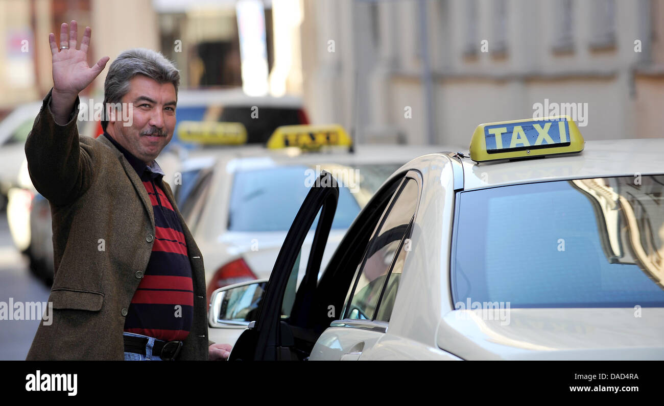 cab driver necmi akdolan smiles and presents his taxi in munich stock photo royalty free image. Black Bedroom Furniture Sets. Home Design Ideas