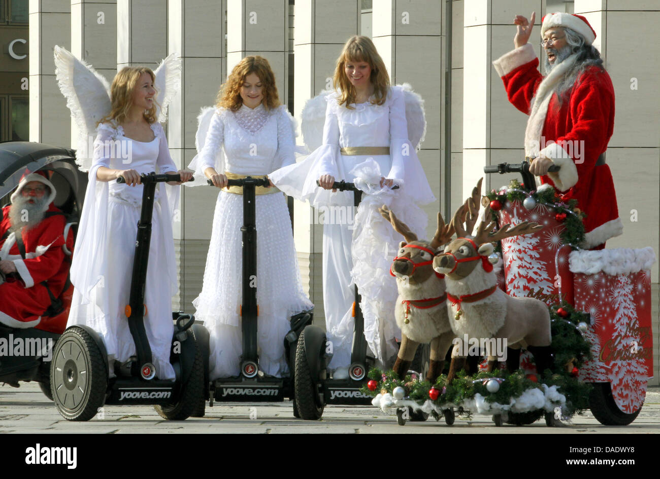 Christmas angels and a santa claus pose on segways in