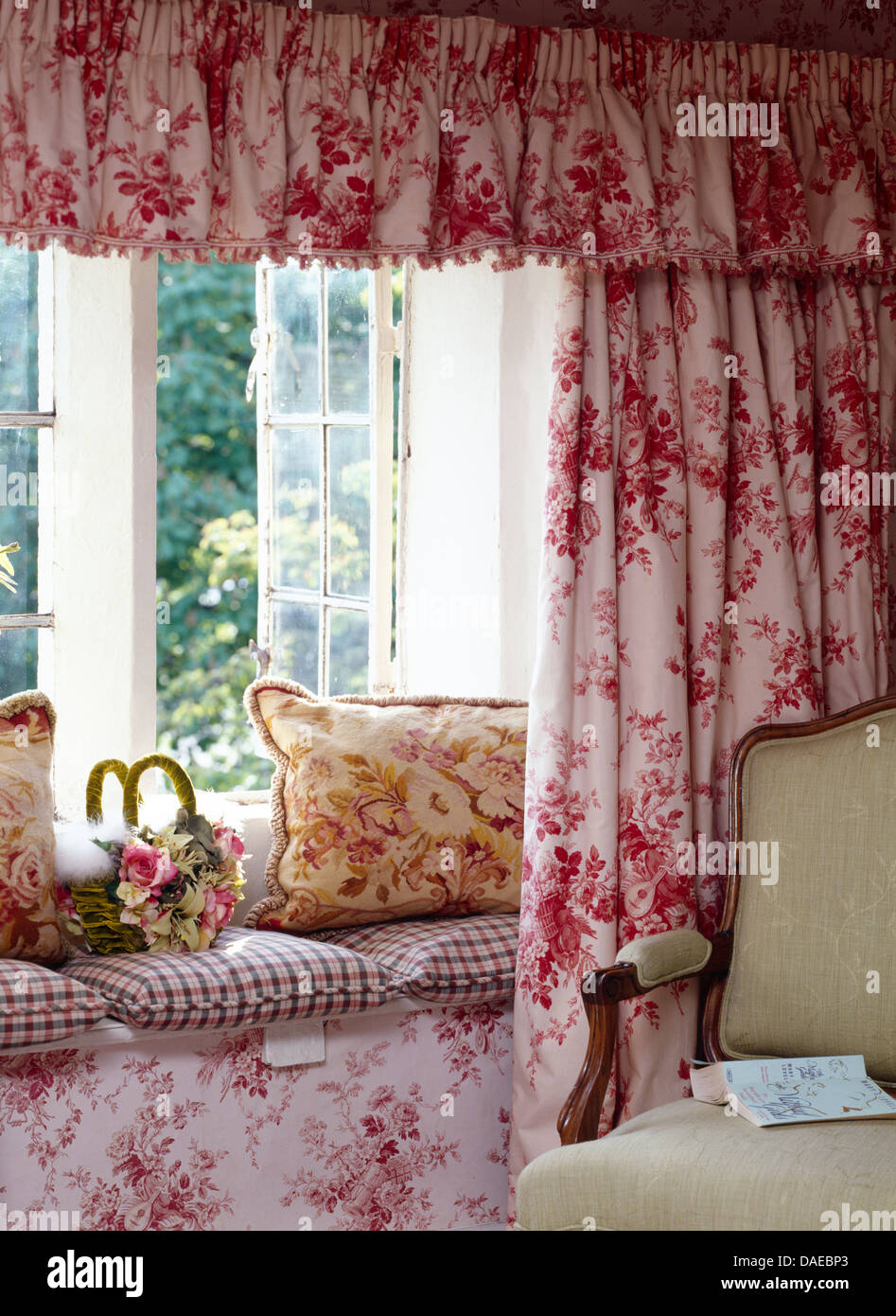 Cottage curtains - Pink Floral Curtains And Pelmet On Open Window Above Window Seat With Floral And Checked Cushions In Cottage Living Room