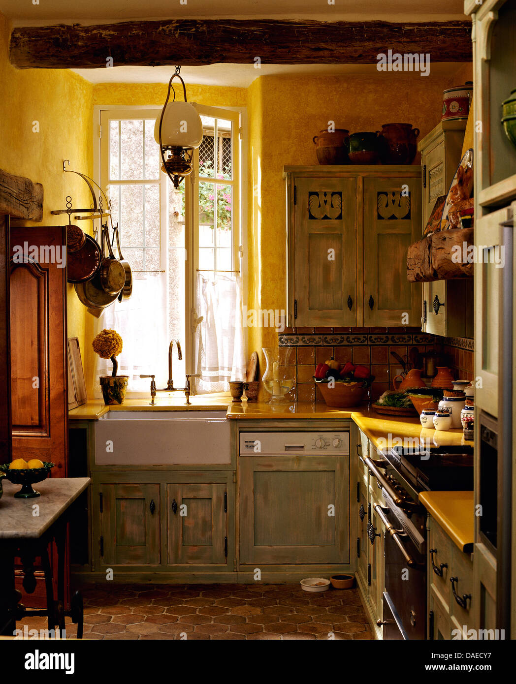 French country kitchen green - Pale Gray Green Distressed Cupboards In Yellow French Country Kitchen With Terracotta Tiled Floor And Belfast Sink