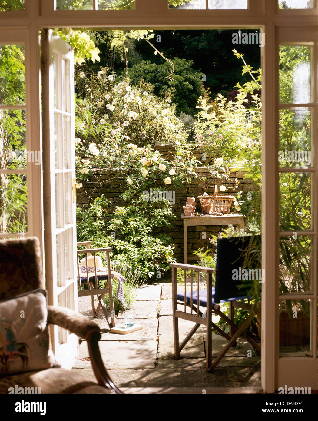 Cottage sitting room with open french doors to garden with chairs cottage sitting room with open french doors to garden with chairs on patio and pink roses on the wall rubansaba