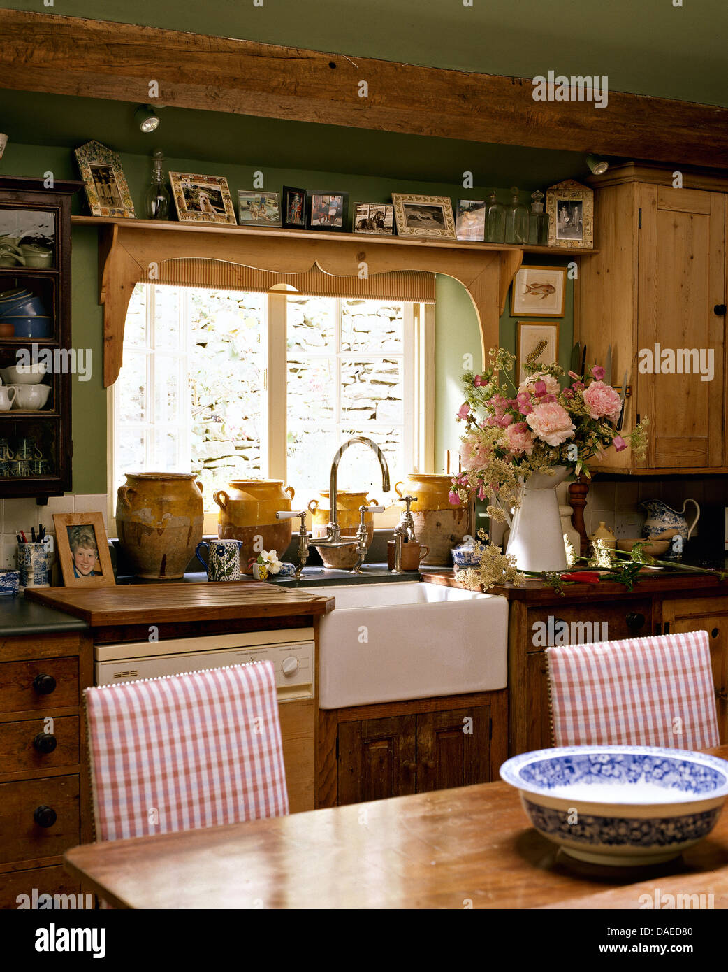 Photographs on shelf above window and Belfast sink in cottage kitchen with  checked upholstered chairs at simple wood table