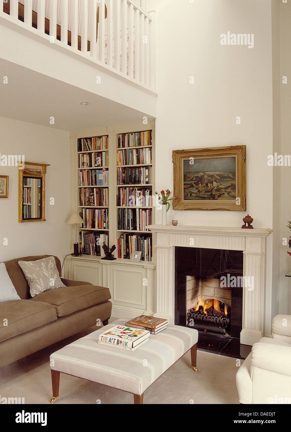 Beige sofa and upholstered stool in front of fireplace in white ...