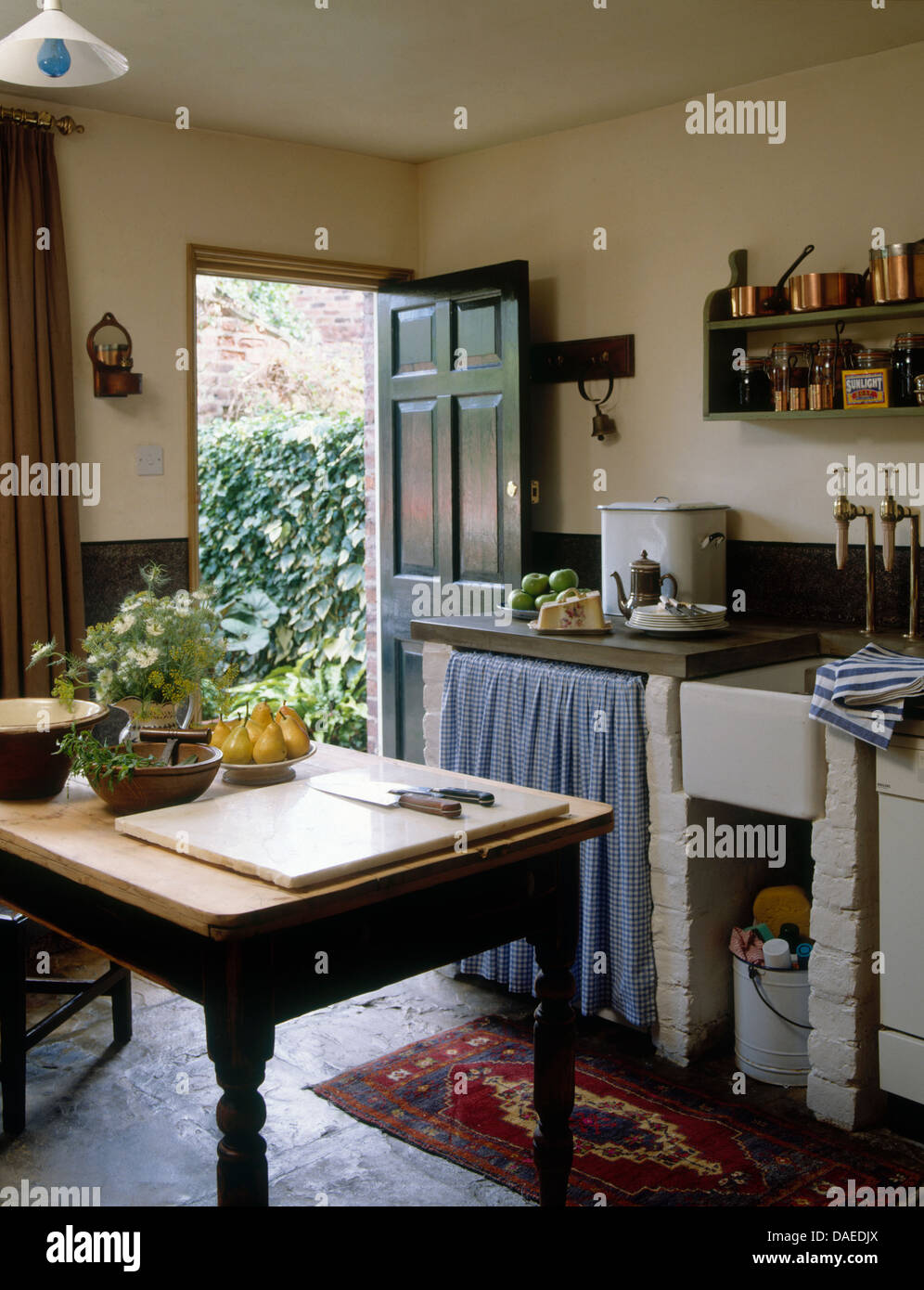 Wooden table in center rustic country cottage kitchen with curtains on unit  beside Belfast sink