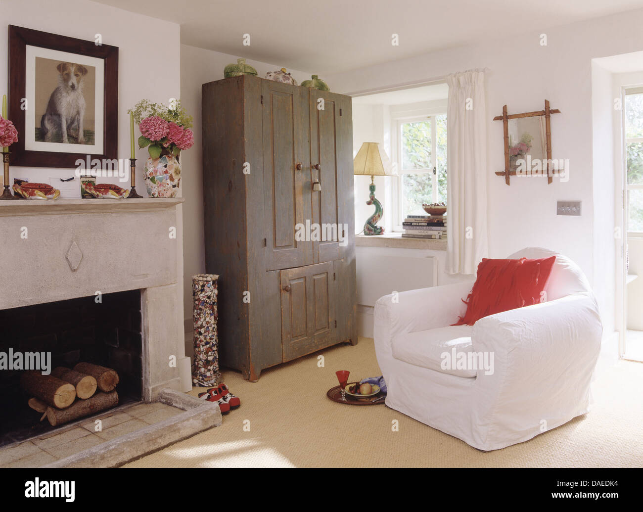 white armchair and gray painted cupboard in white cottage living