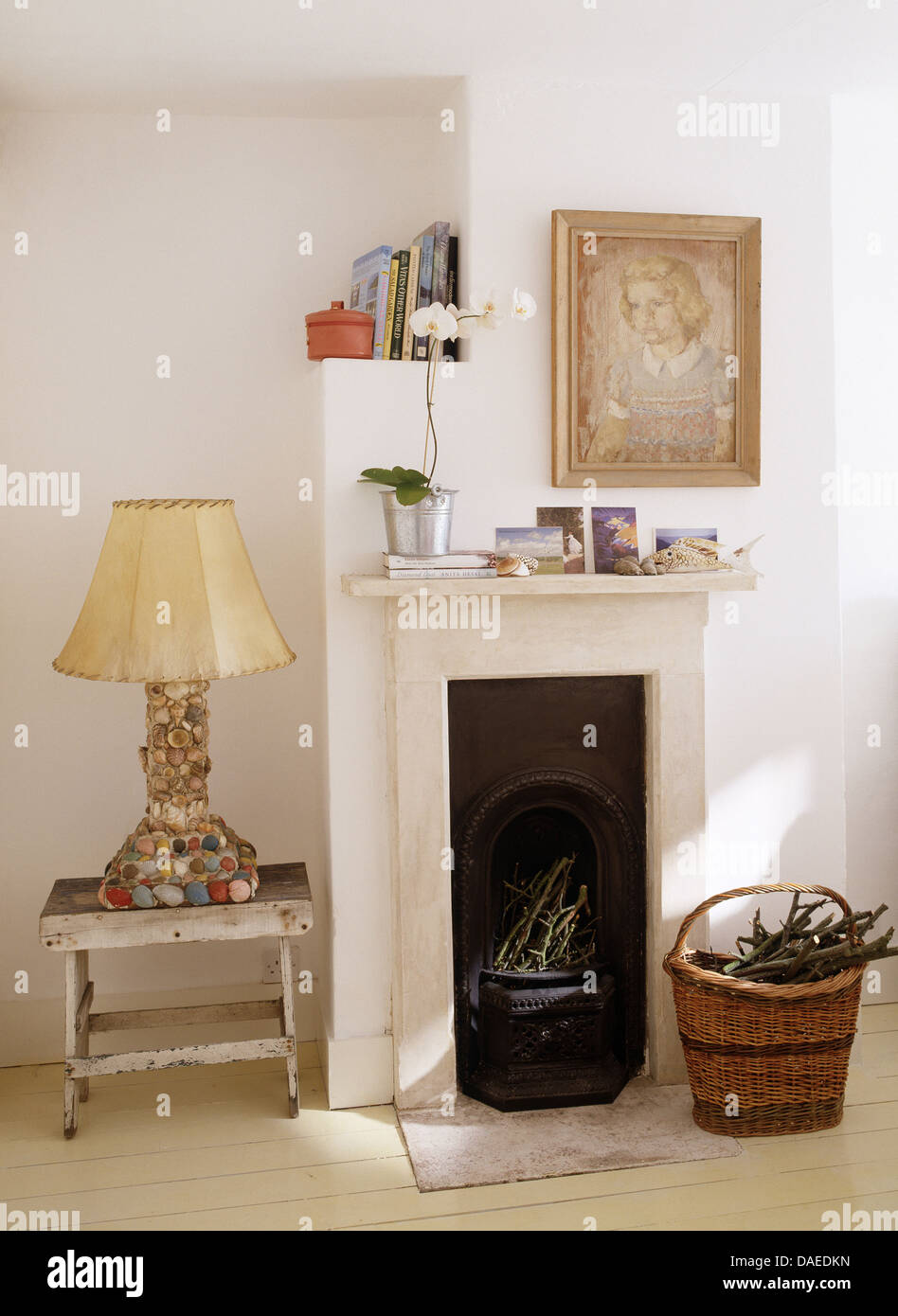 Pebble encrusted lamp on painted stool beside small fireplace in ...