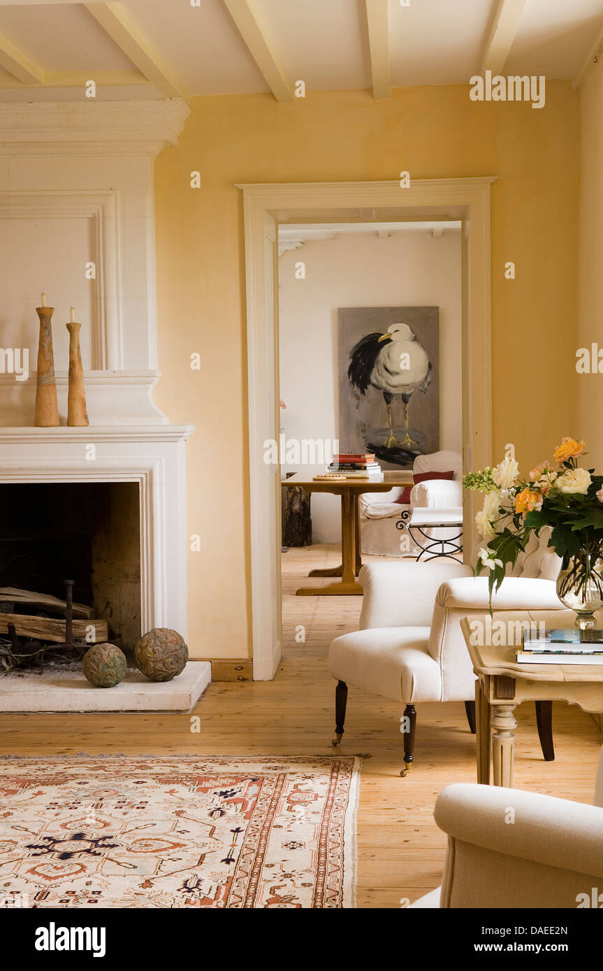 Cream Upholstered Armchair Beside Fireplace In French Country Sitting Room With Open Door To Dining