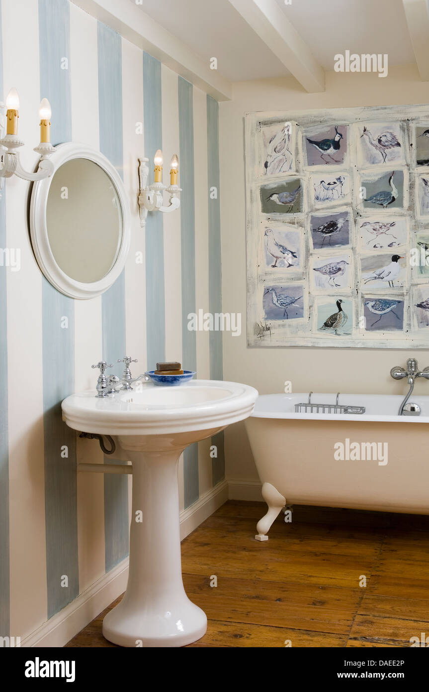 Pedestal Washbasin Next To And Roll Top Bathtub In Traditional Bathroom  With Blue Striped Wallpaper And Wooden Flooring
