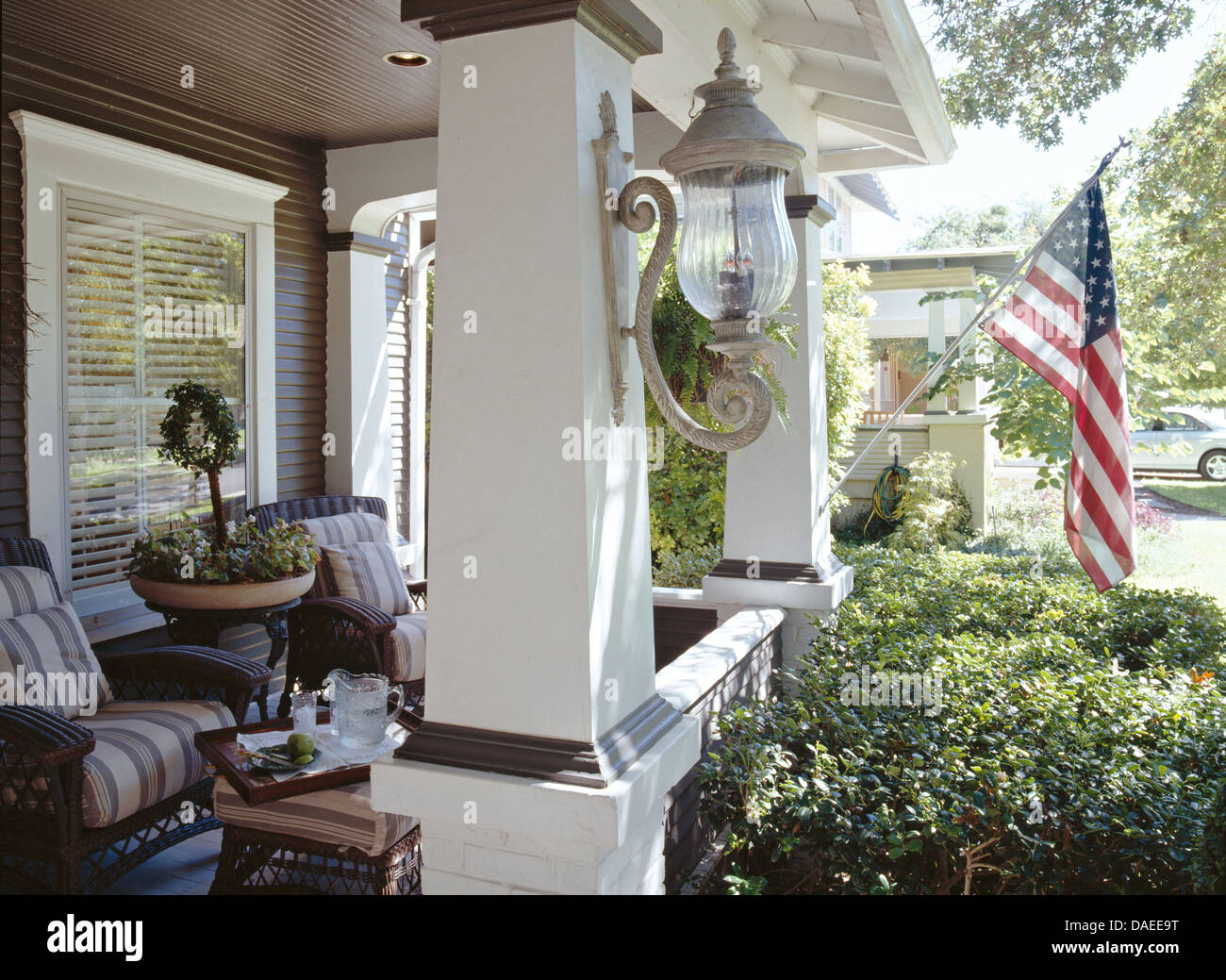 lamp and american flag on pillars of american colonial style house