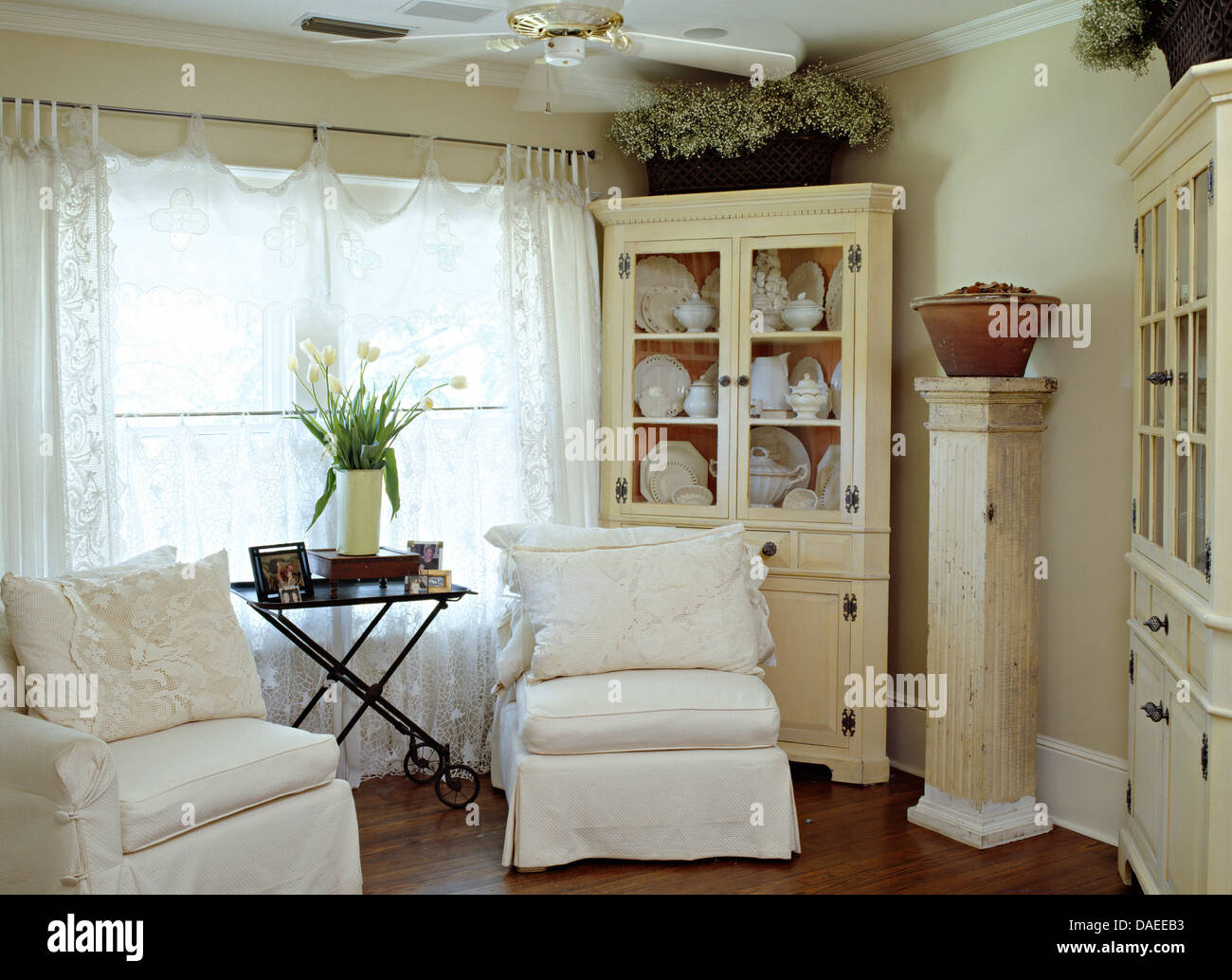 Cottage curtains - Stock Photo White Loose Covers On Chairs In Front Of Window With Lace Curtains In Cottage Living Room With Painted Dresser And Tall Pedestal