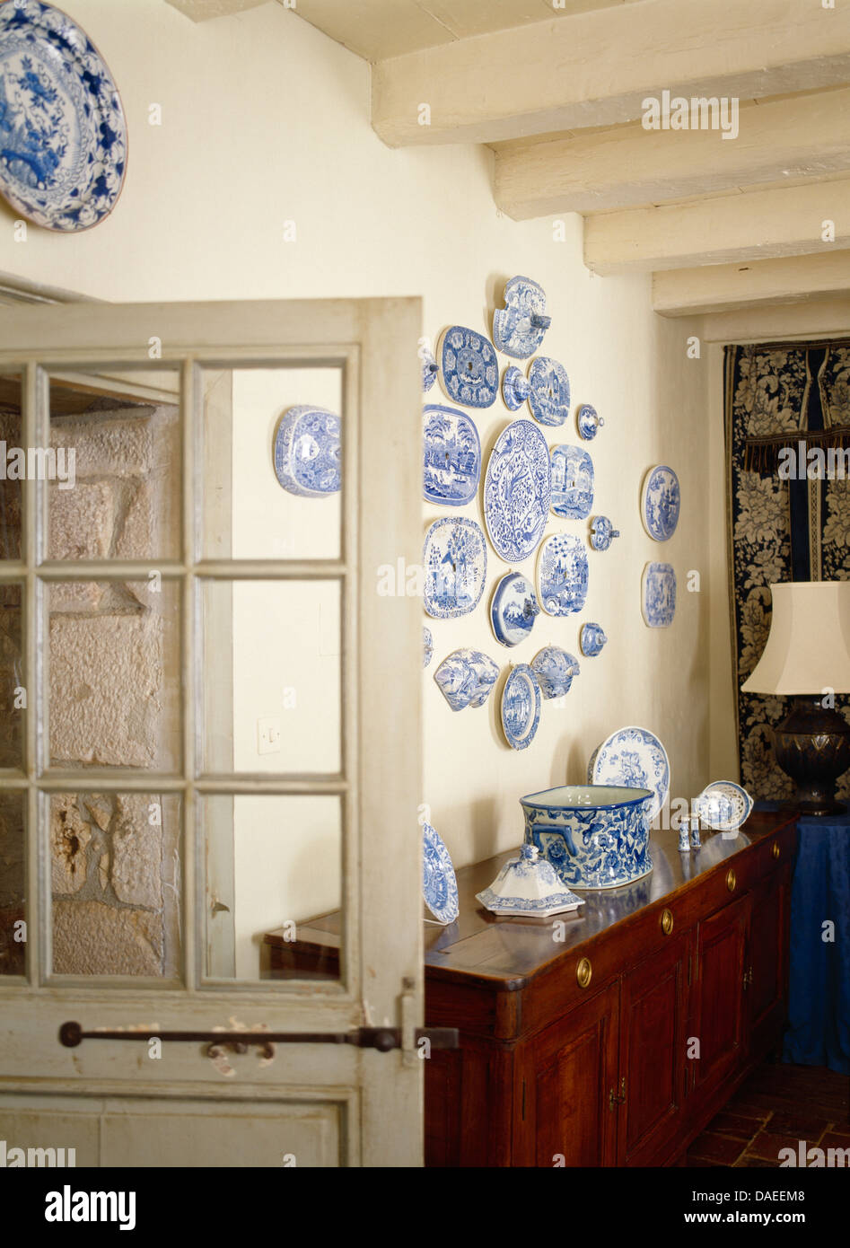 Half Glazed Door Beside Sideboard Below Collection Of Blue And