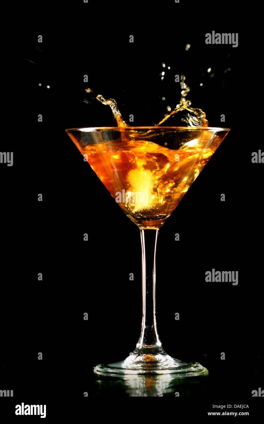 alcohol splash in martini glass on black background stock