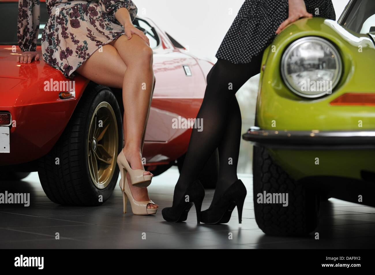 Two modesl sit, cross-legged, on classic cars (l-r, Lancia Stratos ...