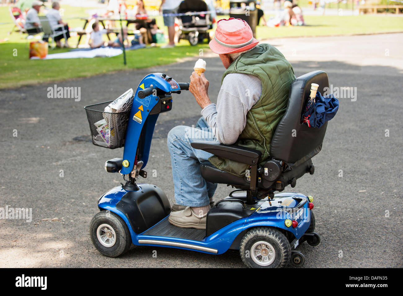Elderly man on mobility scooter watches young people have for Motorized cart for seniors