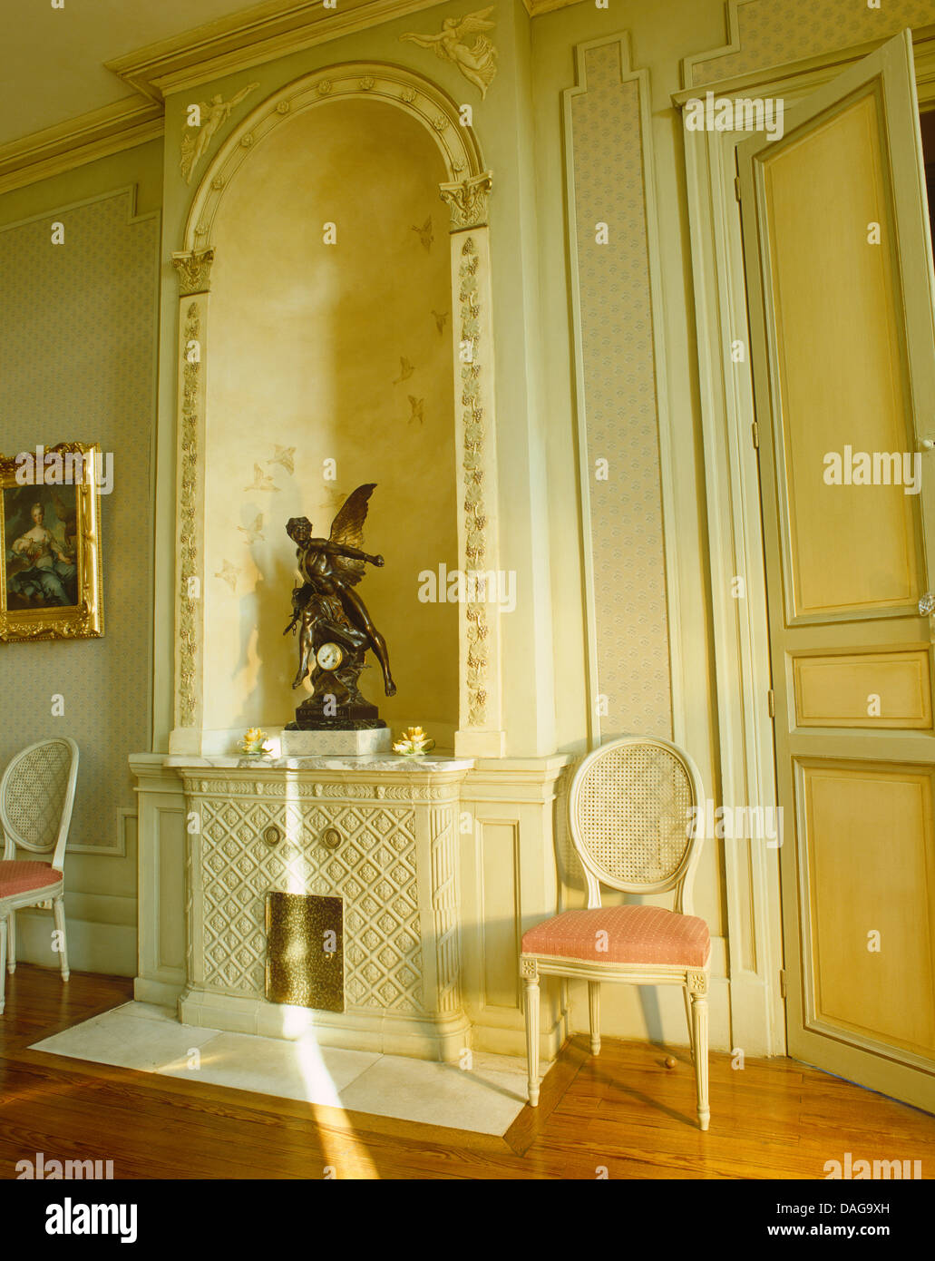bronze statue in alcove above decorative fireplace in french country hall with painted balloon back chairs - Decorative Fireplace