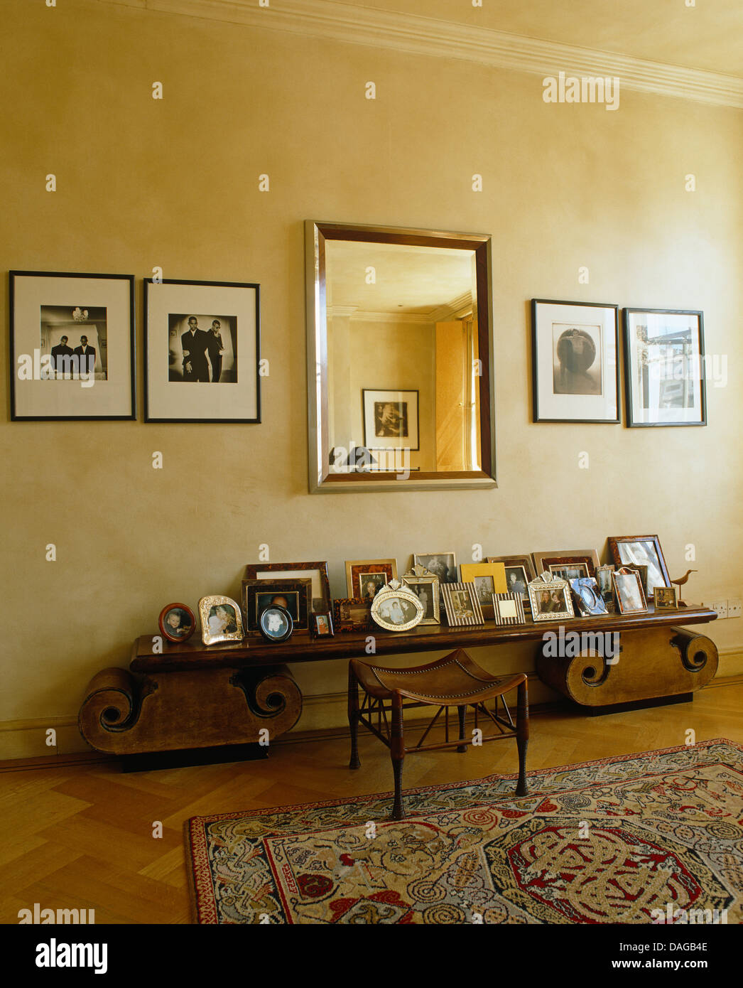 Framed Black+white Photographs On Either Side Of Mirror Above Low Console  Table With Framed Family Photographs In Modern Bedroom