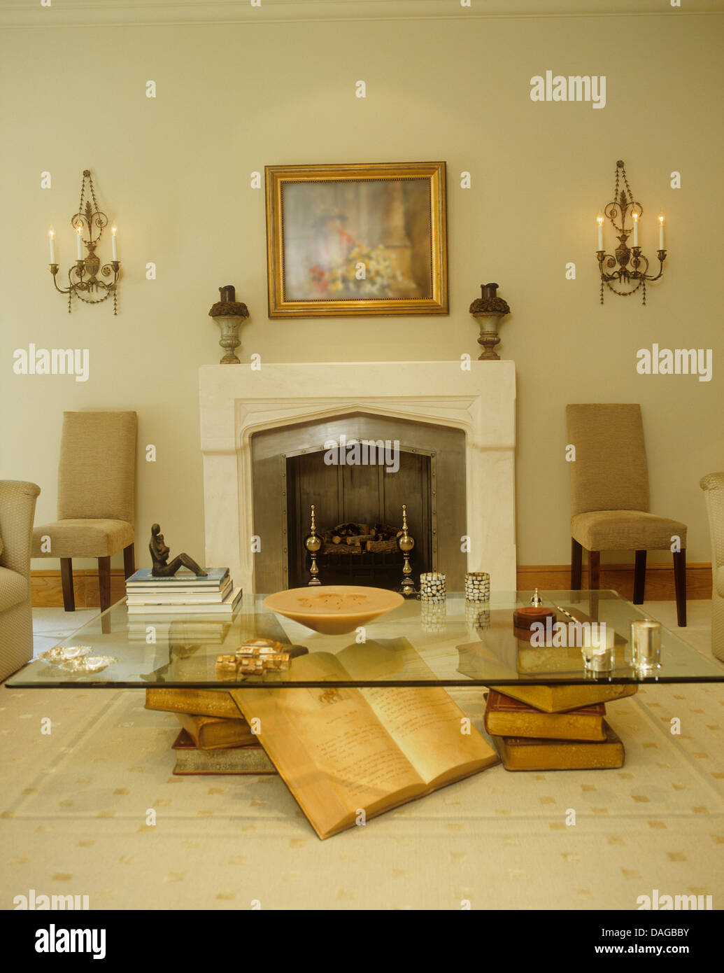 wall glass living room tables. Glass coffee table and book sculpture in modern living room with wall  lights on either side of stone fireplace