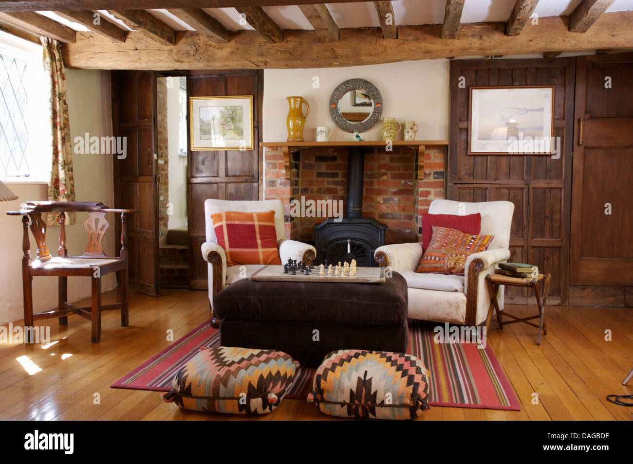 Kelim Upholstered Stools And White Armchairs Arranged Around Brown Ottoman In Beamed Cottage Living Room With Wooden Flooring